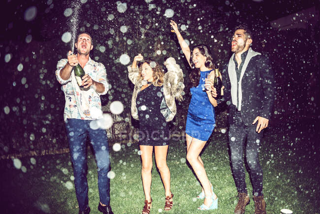 Giovane uomo che apre champagne mentre gli amici ballano all'aperto in festa di notte — Foto stock