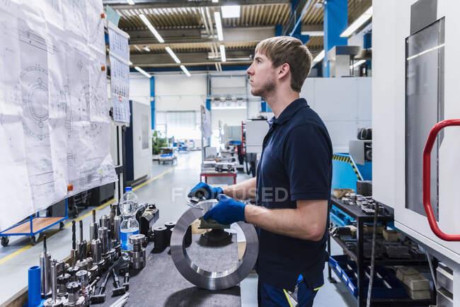 Hombre trabajando en un banco de trabajo en una fábrica metalúrgica - foto de stock