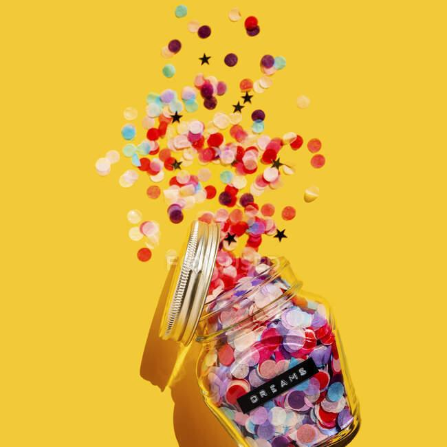 Colorati coriandoli versati dal barattolo di vetro — Foto stock