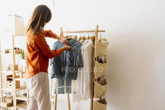 Жіночий дизайнер моди працює вдома з партою для одягу. — стокове фото