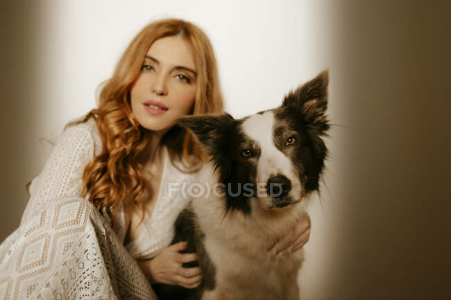 Блондинка дома в пижаме с пограничной собакой колли — стоковое фото
