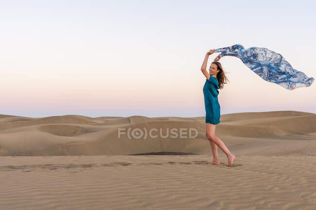 Щаслива жінка, яка тримає тканину під час заходу сонця в дюнах (Гран - Канарія, Іспанія). — стокове фото