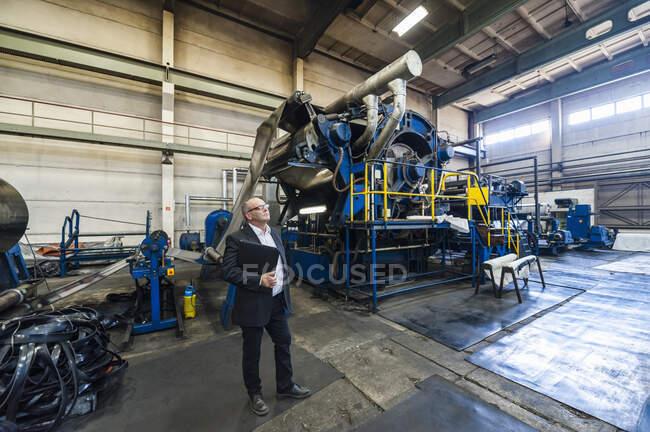Старший бізнесмен на каучуковій фабриці. — стокове фото