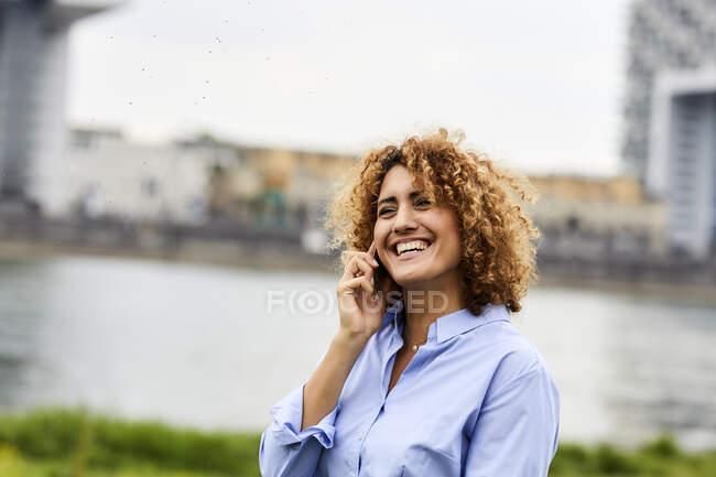 Mulher de negócios usando smartphone na beira do rio em Colônia, Alemanha — Fotografia de Stock