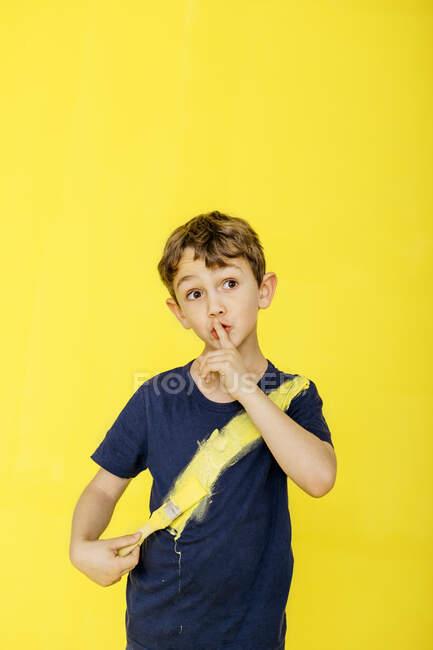 Garçon mignon utilisant pinceau sur t-shirt tout en se tenant avec le doigt sur les lèvres sur fond jaune — Photo de stock