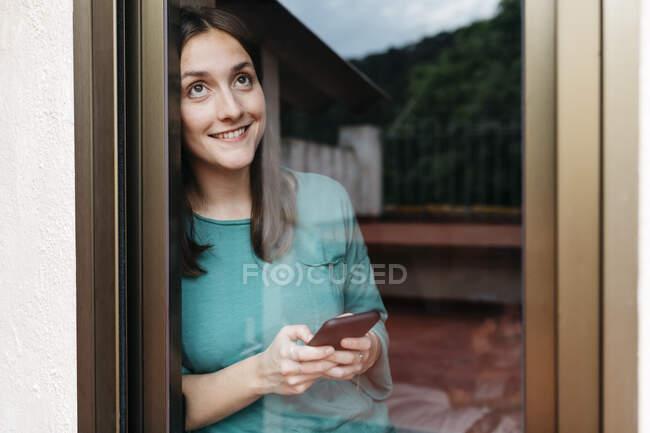 Frau mit Smartphone am Fenster, Mann mit Laptop zu Hause im Bett — Stockfoto