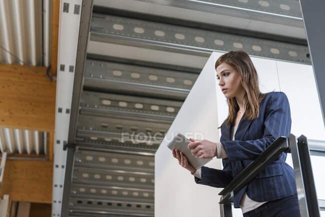 Безробітна жінка тримає цифрову табличку, озираючись, стоячи на заводі. — стокове фото