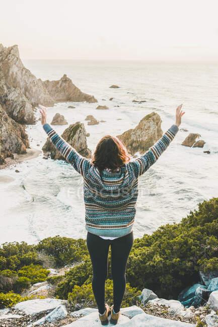 Giovane donna in piedi con le braccia tese sulla roccia a Ursa Beach, Regione di Lisboa, Portogallo — Foto stock
