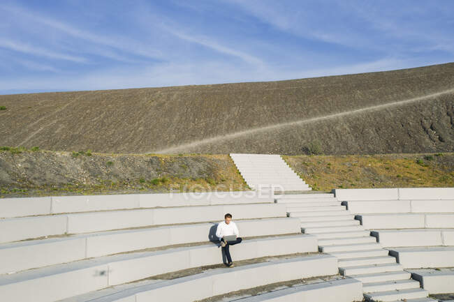 Empresario sentado con portátil en el anfiteatro BergArena pasos contra el cielo en un día soleado - foto de stock