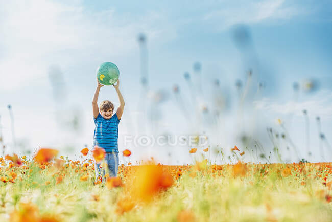 Happy boy holding globe while standing in poppy field against sky on sunny day — Stock Photo