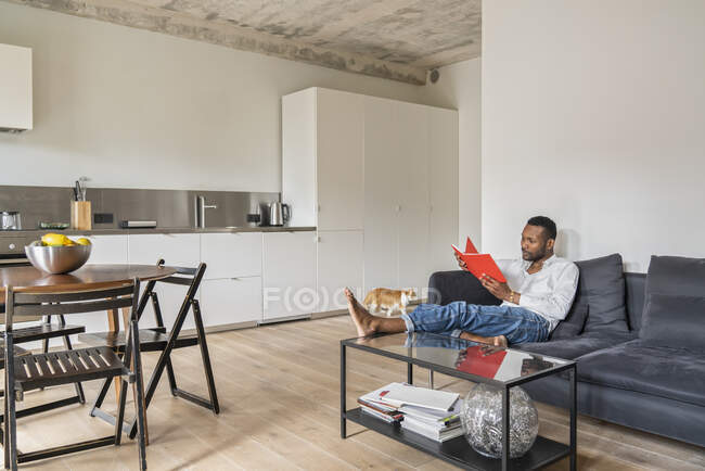Мужчина сидит на диване в современной квартире и читает книгу — стоковое фото