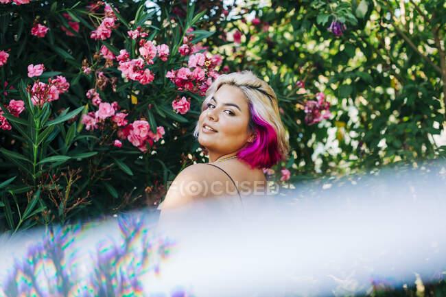 Mujer joven de pie cerca de la planta con flores al aire libre - foto de stock