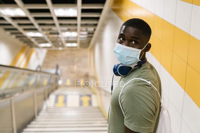 Jeune homme portant un masque regardant loin tout en se tenant sur les marches dans la station de métro — Photo de stock