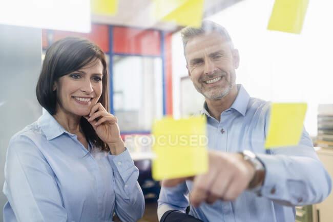 Усміхнена комерсантка і бізнесмен дивляться на клейкі банкноти у фабриці. — стокове фото