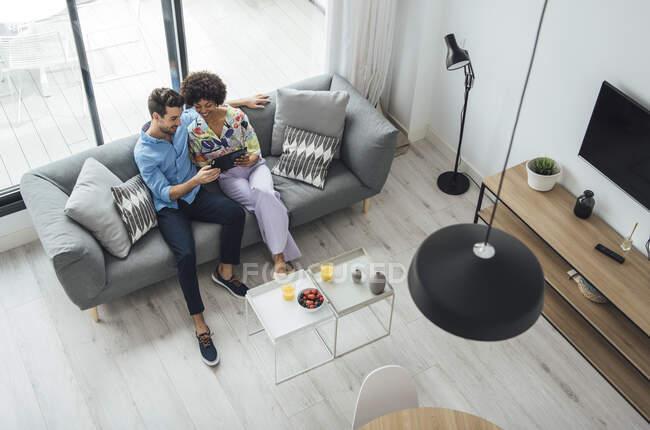 Мультиэтническая пара с помощью цифрового планшета, сидя на диване в гостиной современного пентхауса — стоковое фото