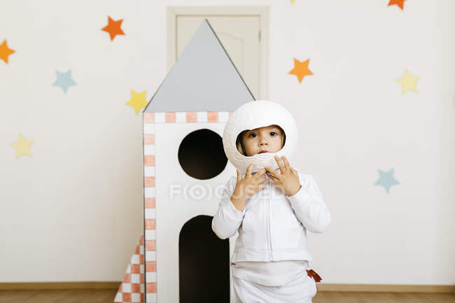 Girl wearing costume and playing astronaut at rocket — Stock Photo