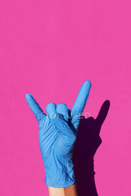 Рука жінки в латексних рукавичках, що роблять знак рогів. — стокове фото