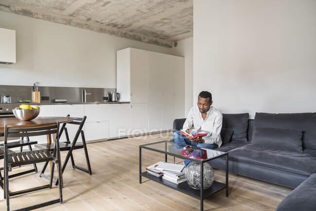 Мужчина сидит на диване в современной квартире, переворачивая страницы в книге — стоковое фото