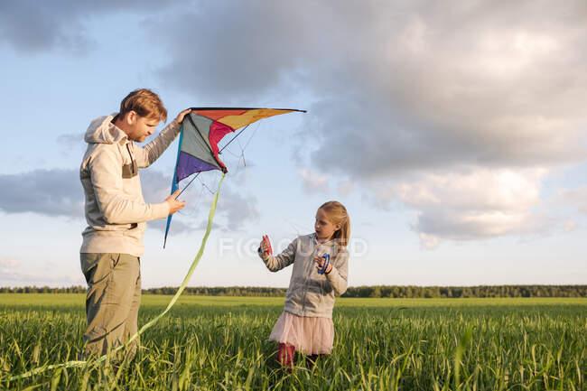 Отец и дочь летят воздушным змеем, стоя на зеленом ландшафте на фоне неба — стоковое фото