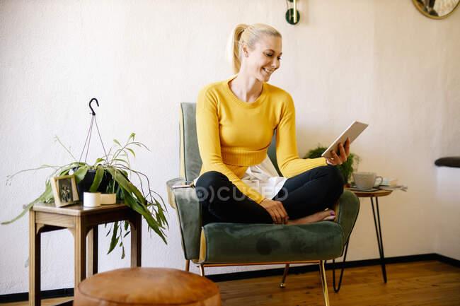 Donna bionda sorridente seduta su una poltrona a casa con tablet digitale — Foto stock