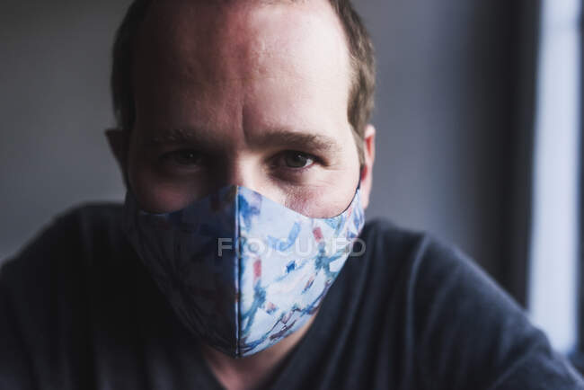 Close-up of mid adult man wearing mask against wall at home — Stock Photo