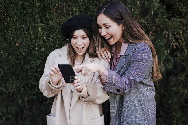 Dos mujeres emocionadas mirando el teléfono celular - foto de stock