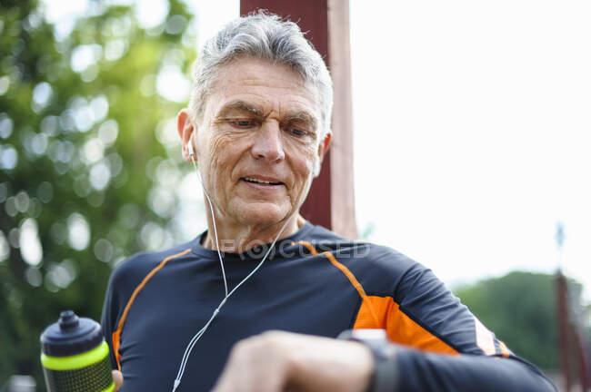 Hombre mayor comprobando el tiempo mientras camina en el parque - foto de stock