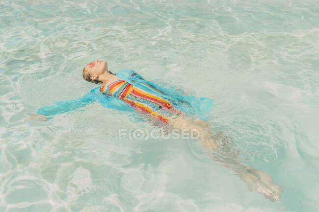 Donna vestita galleggiante sull'acqua in piscina — Foto stock