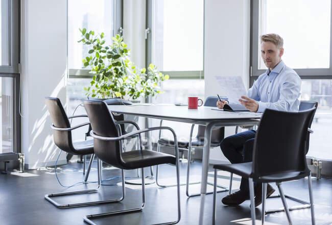 Бізнесмен сидить за столом у конференц-залі і читає газети. — стокове фото