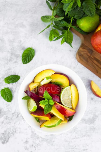 Ensalada de frutas con melocotón, lima y menta - foto de stock