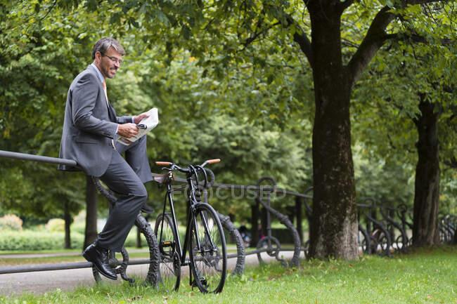 Empresario leyendo periódico mientras está sentado en la barandilla en el parque público - foto de stock