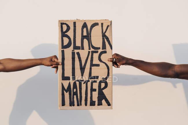 Руки, що тримають чорне життя мають значення — стокове фото