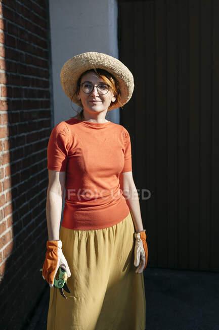 Retrato de mujer madura con guantes de jardinería y podadora de pie a la luz del sol - foto de stock