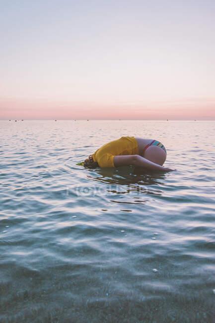 Vista laterale della ragazza adolescente che si gode in mare contro il cielo durante l'alba — Foto stock