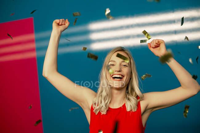 Allegro bella donna con le braccia alzate danza tra coriandoli in festa — Foto stock