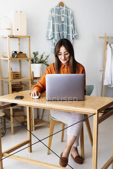 Créatrice de mode féminine travaillant à la maison assis au bureau avec ordinateur portable — Photo de stock