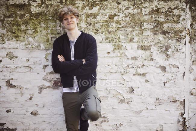 Porträt eines lächelnden jungen Mannes mit blonden Locken vor verwitterter Wand — Stockfoto
