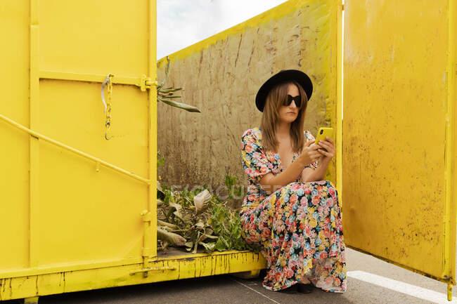 Женщина в цветочном платье, сидит в желтом контейнере, используя смартфон — стоковое фото