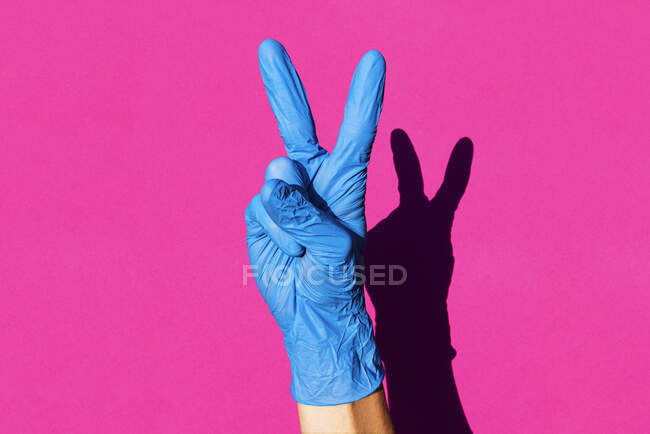Жінка в латексних рукавичках робить V знак — стокове фото