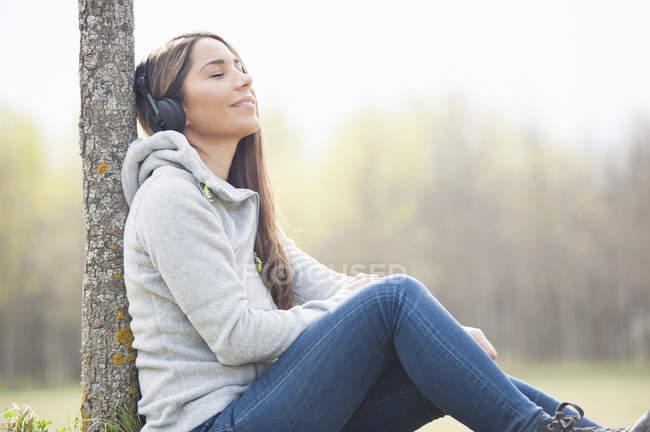 Femme détendue écoutant de la musique tout en s'appuyant sur le tronc d'arbre au parc — Photo de stock