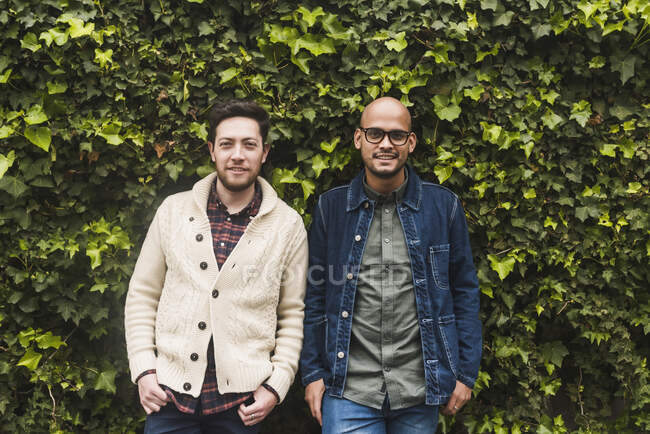Gay couple standing against plants in park — Stock Photo