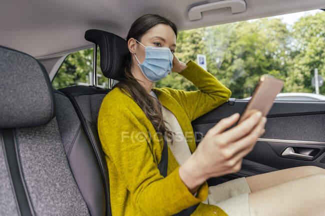 Mujer joven con máscara protectora sentada en el asiento trasero del coche mirando el teléfono celular - foto de stock