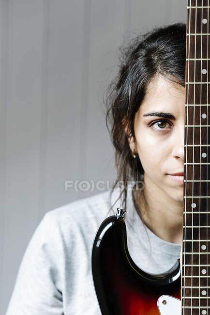 Jeune femme cachée derrière la guitare électrique contre le mur à la maison — Photo de stock