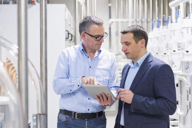 Dos empresarios con tableta discutiendo en una fábrica - foto de stock