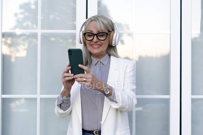 Mujer de negocios alegre usando el teléfono inteligente mientras escucha música a través de auriculares contra la puerta de la oficina - foto de stock