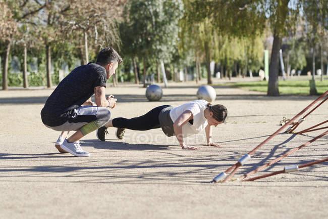 Женщина во время тренировки с тренером в парке — стоковое фото