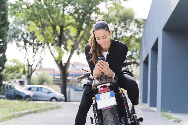 Усміхнена жінка сидить на мотоциклі і користується смартфоном. — стокове фото