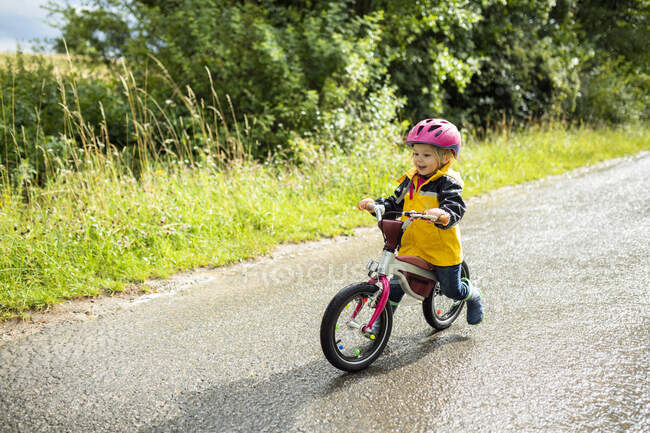 Menina da criança com capacete de ciclismo rosa na bicicleta de equilíbrio — Fotografia de Stock