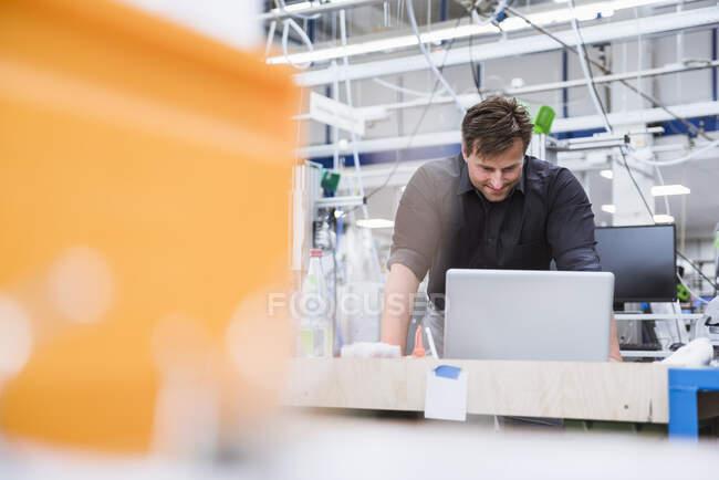 Людина, яка користується ноутбуком на заводі. — стокове фото