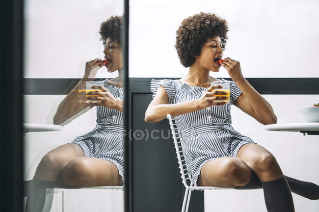 Mulher comendo morango enquanto se senta na cadeira na varanda na cobertura — Fotografia de Stock